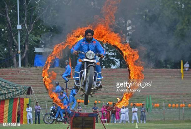 An Indian police member on motorcycle jumping through a ring of fire during the official celebrations for India's Independence Day at Bakshi Stadium...