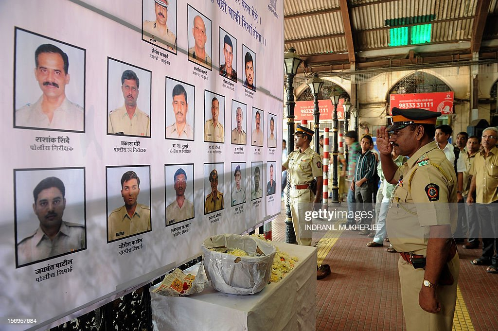 An Indian police officer pays his respects to police and uniformed personnel who lost their lives in 2008 terror attacks outside a railway station in Mumbai on November 26, 2012. A total of 166 people were killed and more than 300 others were injured when 10 heavily-armed Islamist militants stormed the city on November 26, 2008, attacking a number of sites, including the city's main railway station, two luxury hotels, a popular tourist restaurant and a Jewish centre. AFP PHOTO/ INDRANIL MUKHERJEE