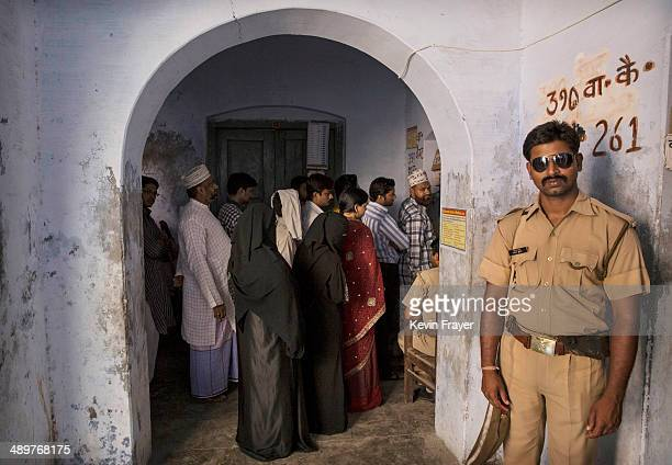 An Indian police officer stands guard as voters wait at a polling station on May 12 2014 in Varanasi India Indians voted in the ninth and final phase...