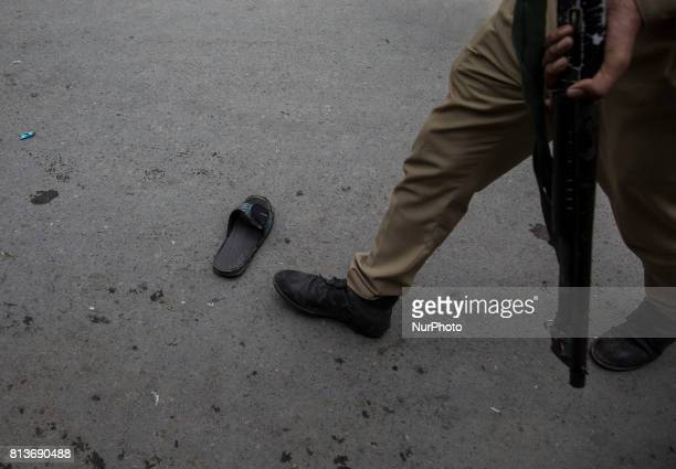 An Indian police officer walk past a lost slipper during funeral procession of a local rebel Sajad Gilkar which was tear gassed Wednesday July 12...