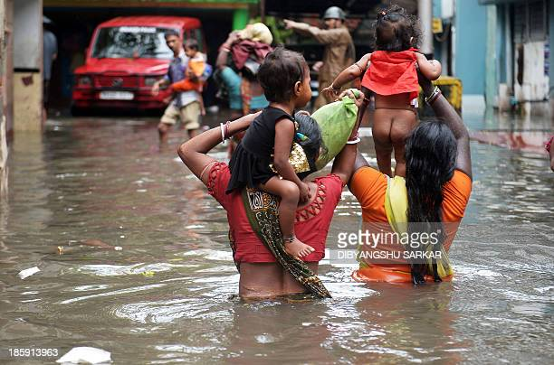 An Indian Police official guides pavement dwellers through waterlogged streets to a to a safer place in Kolkata on October 26 2013 Persistent rain...