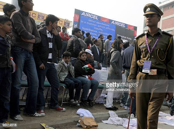 An Indian police official walks among supporters after the cancellation of the fifth and final One Day International cricket match at The Feroz Shah...
