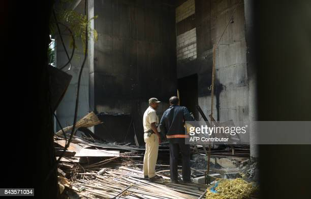 An Indian policeman and fire official inspect the scene of a fire at a building construction site in Mumbai on September 7 2017 Six people were...