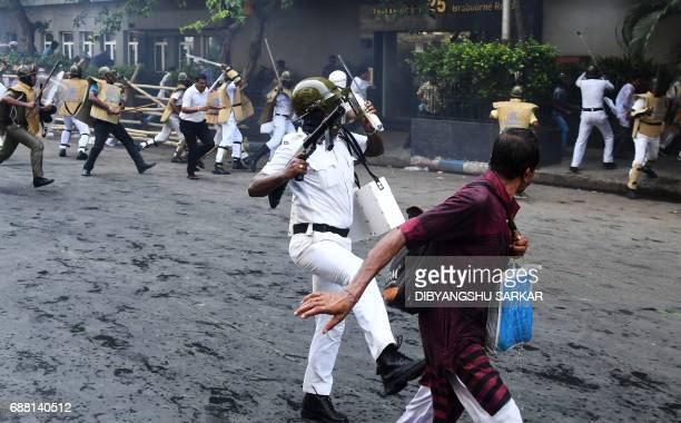 An Indian policeman charges at activists of the Bhartiya Janata Party next to the state police headquarters in Kolkata on May 25 2017 The activists...