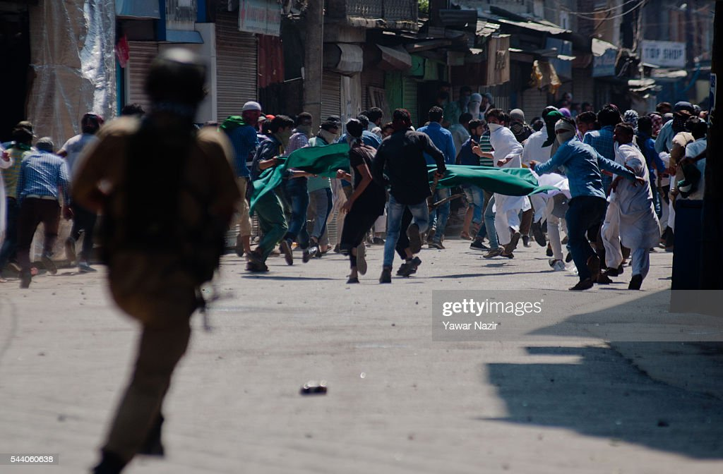 An Indian policeman chase away Kashmiri Muslim protesters during a protest demonstration marking al-Quds (Palestine,) and Kashmir Day an annual event held on the last Friday of the Holy month of Ramadan, as a means to express solidarity with the Palestinians on July 01, 2016 in Srinagar, the summer capital of Indian administered Kashmir, India. Hundreds of thousands of Kashmiri Muslim devotees took part in the mass prayer of the last Friday, or Jummat-ul-Vida, of the holy Islamic month of Ramadan ahead of the Eid al-Fitr festival which marks the end of the fasting month of Ramadan.