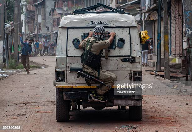 An Indian policeman chases Kashmiri Muslim protesters throwing stones at them during an anti India protest following the weeks of violence that has...