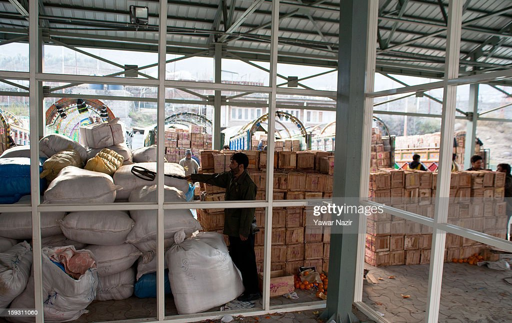 An Indian policeman checks unloaded goods from Pakistani vehicles with his metal detector at the trade facilitation centre in the border area near Uri on January 11, 2013 in Salamabad, 120 km (75 miles) northwest of Srinagar, the summer capital of Indian Administered Kashshmir, India. People living in the mountainous region along the Line of Control (LOC), a military line that divides Indian-administered Kashmir from the Pakistan-administered Kashmir have continually been at risk due to hostility between the armies of the two rival nations, but trade has been carried out smoothly across the Line of Control in North Kashmir. Two Indian and two Pakistani soldiers have been killed in the last week near the Line of Control dividing Kashmir, with both countries blaming each other for the escalating tension.