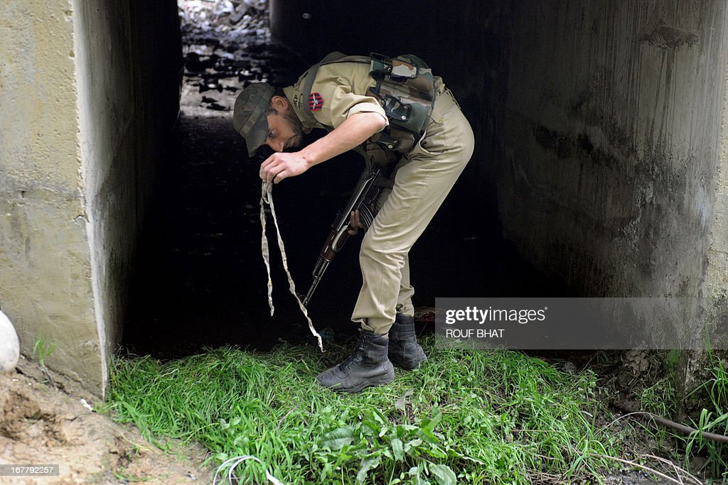 An Indian policeman collects evidence from the scene where an explosive device was found under a culvert on a main road in the outskirts of Srinagar on April 30, 2013. The road leads to frontier areas of disputed Kashmir and is frequently used by the Indian army. The device was later defused by a police bomb disposal squad.