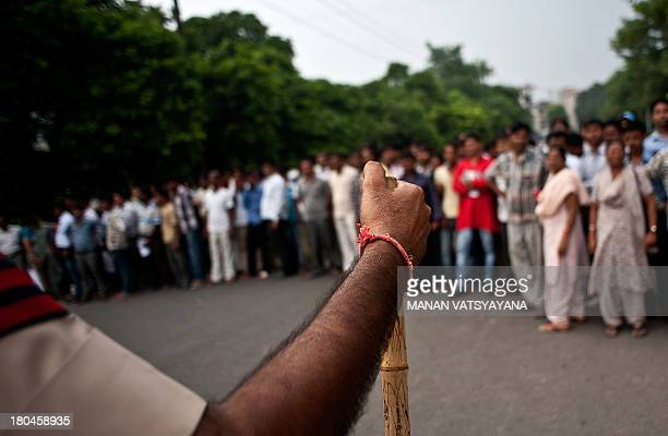 An Indian policeman controls the crowd outside the Saket Court complex following the sentencing of four men convicted of rape and murder in New Delhi...