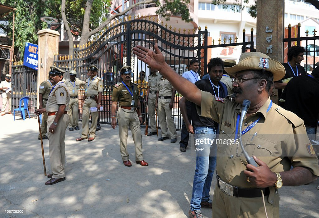 An Indian policeman directs public vehicles away from the main gate of The M. Chinnaswamy Stadium in Bangalore on December 25, 2012. Police were out in full force in the southern Indian city as part of a massive security operation ahead of Pakistan's first cricket tour of India for five years. AFP PHOTO/Manjunath KIRAN