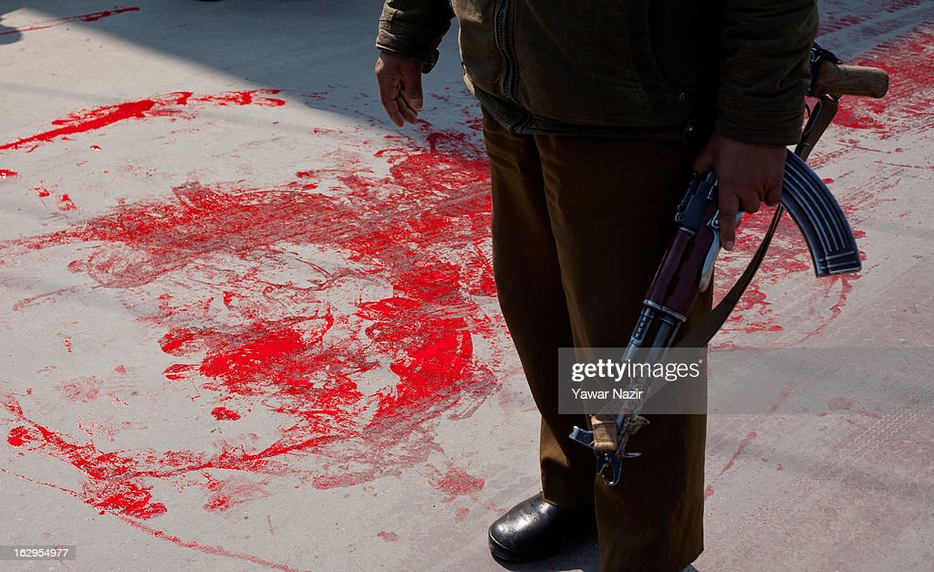 An Indian policeman frisks a Kashmiri Muslim youth after two of their comrades were killed in north Kashmir Handwra by suspected militant on March 02, 2013 in Srinagar, the summer capital of Indian Administered Kashmir, India. Demonstrators wore red ribbons and painted the roads with red paint as part of a protest by pro-independence groups, such as the JKLF, who are seeking the mortal remains of Afzal Guru, who was hanged by the Indian government on February 9, 2013 for his alleged role in the 2001 attack on the country's Parliament .