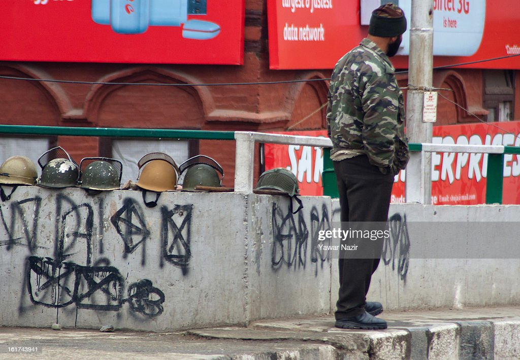 An Indian policeman guards deserted streets next to the helmets of his colleagues during a strict curfew on the seventh consecutive day, imposed after the execution of alleged Indian parliament attacker Mohammad Afzal Guru on February 15, 2013 in Srinagar, the summer capital of Indian Administered Kashmir, India. Afzal Guru, from Sopore town in the north of Kashmir, was hung on February 09 for his role in the 2001 Indian parliament attack which left 14 dead. The hanging has further strained relations between India - who blamed the attack on 'Pakistan backed' militant group Jaish-e-Mohammed - and neighbouring Pakistan and has seen an military increase from both along the border.Curfew was lifted from some parts of Srinagar after four days.