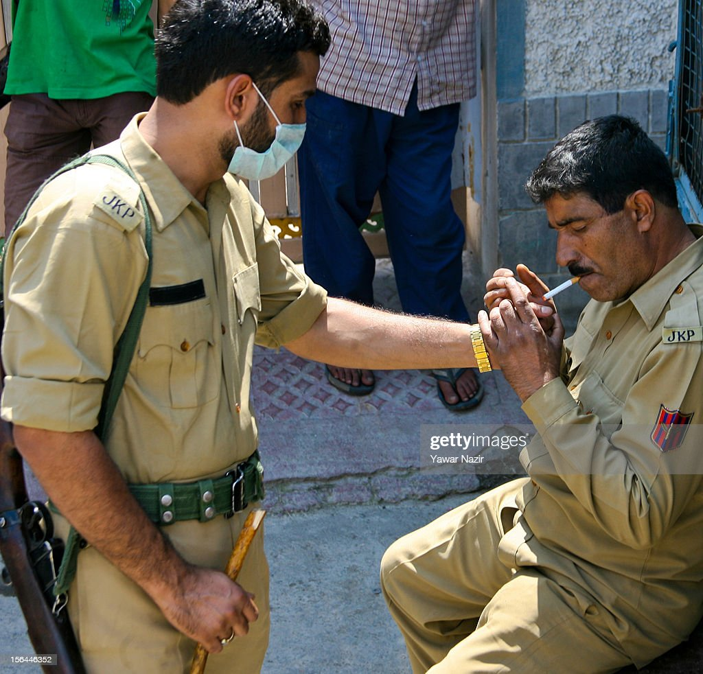 An Indian policeman lights the cigarette of his colleague sitting on an armored vehicle in a public place on November 15, 2012 in Srinagar, the summer capital of Indian administered Kashmir, India. Despite ban on smoking in public places Indian law enforcers often defy government order.
