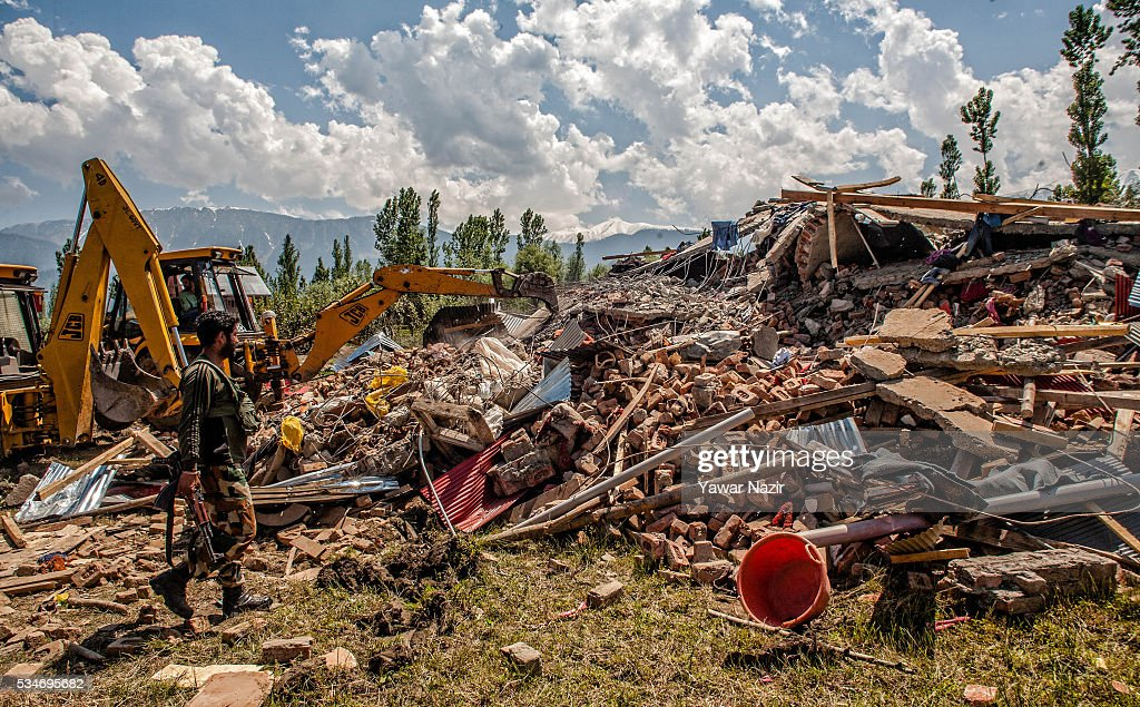 An Indian policeman looks for the arms and ammunitions from a ravaged residential house after a gun battle between militants and Indian government forces on May 27, 2016 in Khonchpur, 40 kilometers (25 miles) west of Srinagar, the summer capital of Indian administered Kashmir, India. Six rebels and an Indian army soldier were killed in two separate gun battles in the north Kashmir just four days after the Indian police claimed to have gunned down two unidentified militants in Sarai Bala area of Srinagar, a claim contested by the locals who say they were just students putting up in the locality.