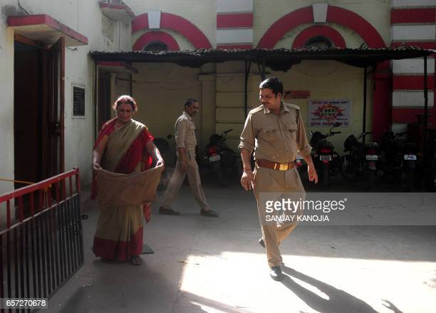 An Indian policeman looks on as a member of staff shakes dust from a floor mat at Civil Lines police station in Allahabad on March 24 2017 The...