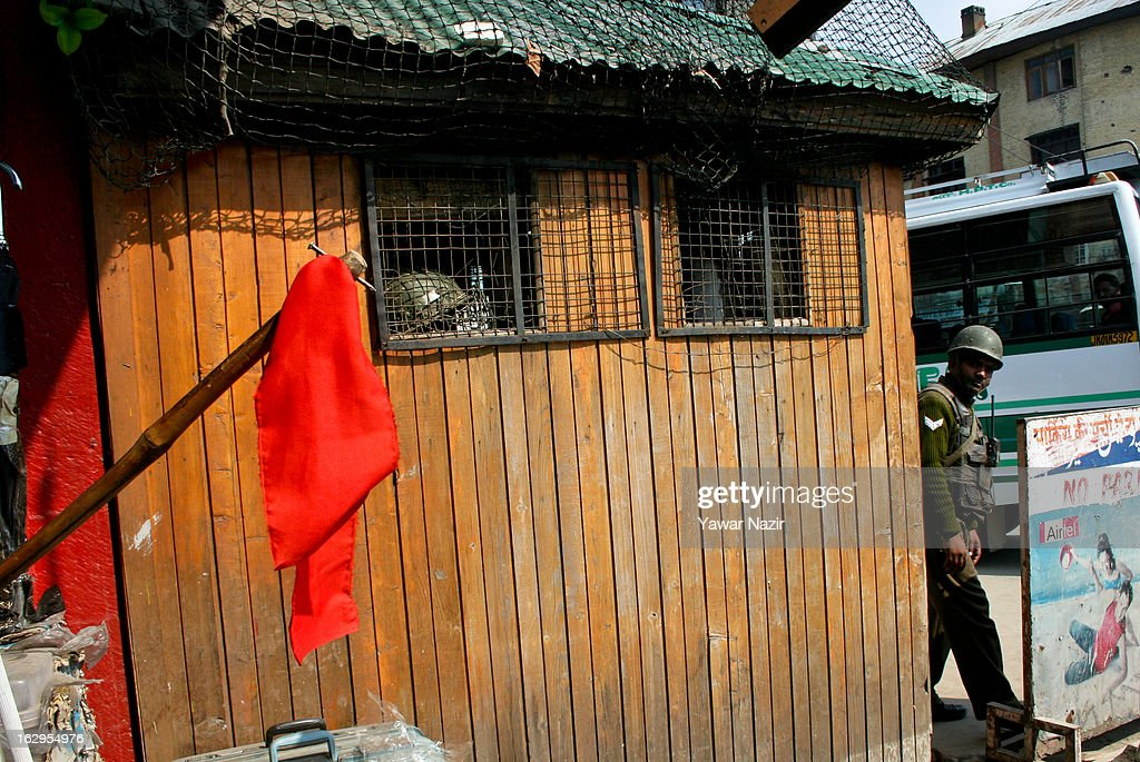 An Indian policeman looks towards a red ribbon hoisted by a Kashmiri Muslim shopkeeper next to the bunker of Indian paramilitary forces on March 02, 2013 in Srinagar, the summer capital of Indian Administered Kashmir, India. Demonstrators wore red ribbons and painted the roads with red paint as part of a protest by pro-independence groups, such as the JKLF, who are seeking the mortal remains of Afzal Guru, who was hanged by the Indian government on February 9, 2013 for his alleged role in the 2001 attack on the country's Parliament .