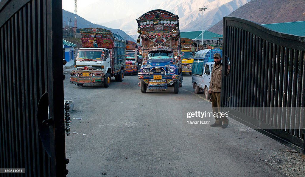 An Indian policeman opens a gate for Pakistani vehicles after unloading their goods at the trade facilitation centre in the border area near Uri on January 11, 2013 in Salamabad, 120 km (75 miles) northwest of Srinagar, the summer capital of Indian Administered Kashshmir, India. People living in the mountainous region along the Line of Control (LOC), a military line that divides Indian-administered Kashmir from the Pakistan-administered Kashmir have continually been at risk due to hostility between the armies of the two rival nations, but trade has been carried out smoothly across the Line of Control in North Kashmir. Two Indian and two Pakistani soldiers have been killed in the last week near the Line of Control dividing Kashmir, with both countries blaming each other for the escalating tension.