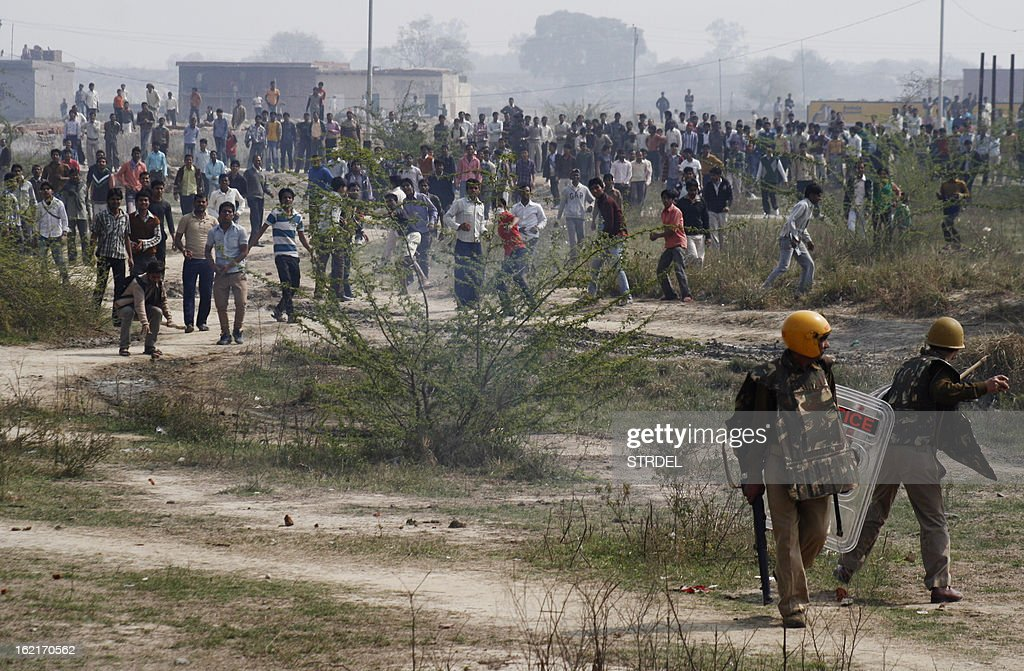 An Indian policeman prepares to throw a stone during a trade union strike in Nodia on the outskirts of New Delhi on February 20, 2013. Cars were burnt and factories were stoned when violence broke out at the all-India trade union strike. Millions of India's workers walked off their jobs in a two-day nationwide strike called by trade unions to protest at the 'anti-labour' policies of the embattled government. Financial services and transport were hit by the strike called by 11 major workers' groups to protest at a series of pro-market economic reforms announced by the government last year, as well as high inflation and rising fuel prices. AFP PHOTO/ STR
