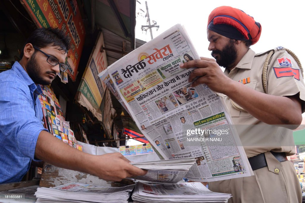 An Indian policeman reads a newspaper, displaying front page headlines of attacks on Christians in Pakistan, at a roadside stall in Amritsar on September 23, 2013. The death toll from a double suicide bombing on a church in Pakistan rose to 81, as Christians protested across the country to demand better protection for their community. The attack on All Saints church in the northwestern city of Peshawar after a service on September 22, which has been claimed by the Pakistani Taliban, is believed to be the deadliest ever to target Pakistan's small Christian minority. AFP PHOTO/NARINDER NANU