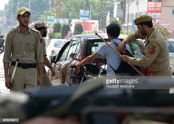 An Indian policeman searches a Kashmiri youth at a checkpoint in Srinagar on August 11 ahead of the country's Independence Day celebrations Indian...