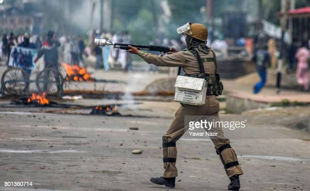 An Indian policeman shoots a teargas canister with his gun at Kashmiri Muslim protesters during an anti India protest on Eidulfitr a festival of...