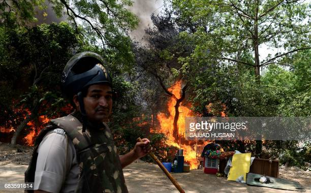 An Indian policeman stands at the site of a fire that broke out in a makeshift settlement in New Delhi on May 16 2017 / AFP PHOTO / SAJJAD HUSSAIN
