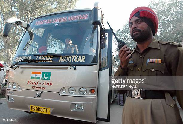 An Indian policeman stands beside a bus carrying local officials on its way to cross the IndiaPakistan border at Wagah in India's northern state of...