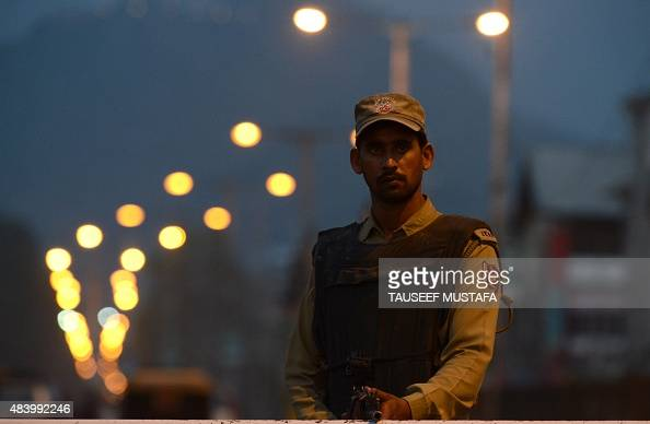 An Indian policeman stands guard during a search operations in Srinagar on August 14 ahead of the country's Independence Day celebrationsIndian...