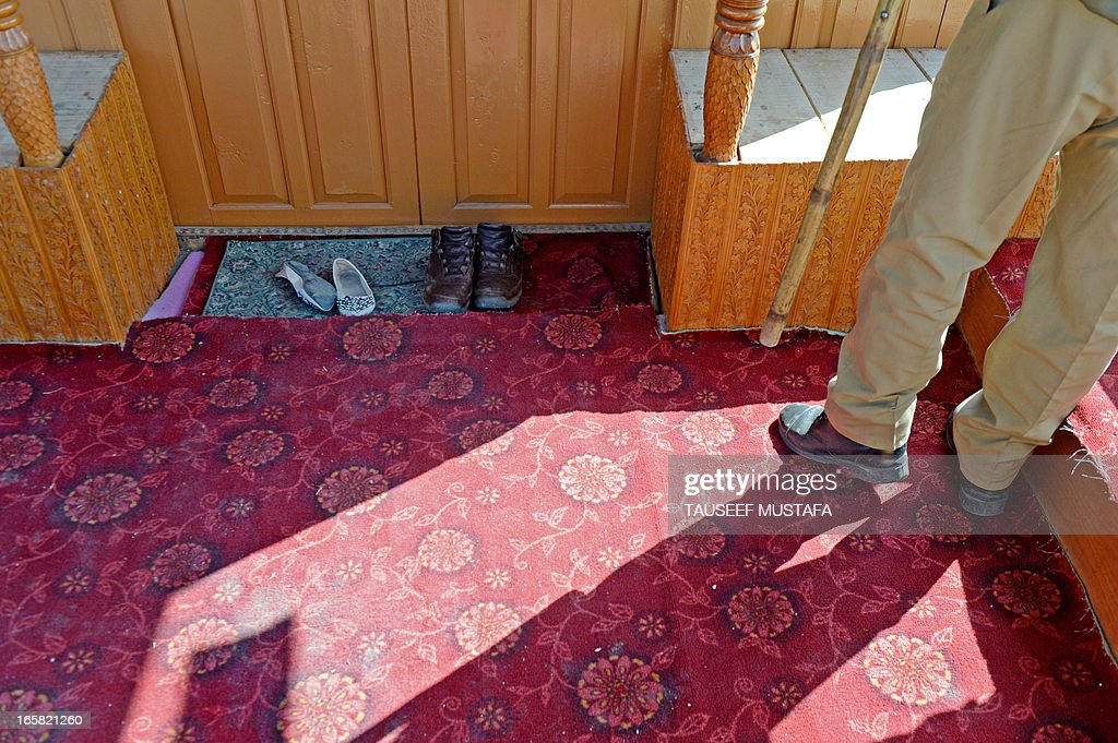 An Indian policeman stands guard on a houseboat near a pair of shoes (L) belonging to a young British woman who was found murdered in Srinagar on April 6, 2013. A British woman holidaying in Indian Kashmir was found dead 'in a pool of blood' on a houseboat and a Dutch man has been arrested on suspicion of her murder, police said on Saturday. The 43-year-old Dutch national was taken into custody as he tried to flee the scenic Kashmir valley in the foothills of the Himalayas, police superintendent Tahir Sajjad told AFP. AFP PHOTO/Tauseef MUSTAFA