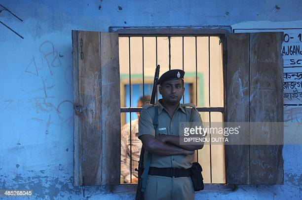 An Indian policeman stands guard outside a polling station as polling worker seal a box containing an Electronic Voting Machine after the polls...