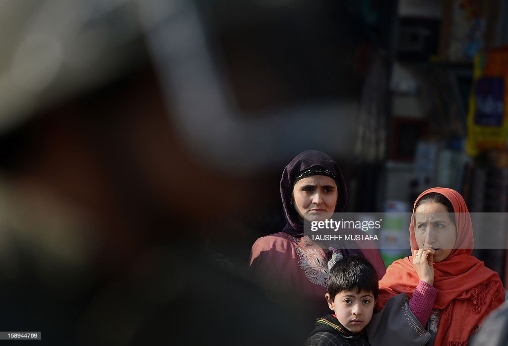 An Indian policeman stands guard,as a Kashmiri muslim family looks on during a protest against a court verdict sentencing two Kashmiris to life imprisonment in Srinagar on January 4, 2013. The Muslim-majority region is in the grip of a 20-year insurgency against rule from New Delhi, which has left more than 47,000 people dead by the official count, a separatists put the toll twice as high. AFP PHOTO/ Tauseef MUSTAFA