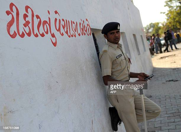 An Indian policeman stands near ticket selling windows with red lettering in Gujarati highlighting 'Sales of Tickets is closed' outside The Sardar...