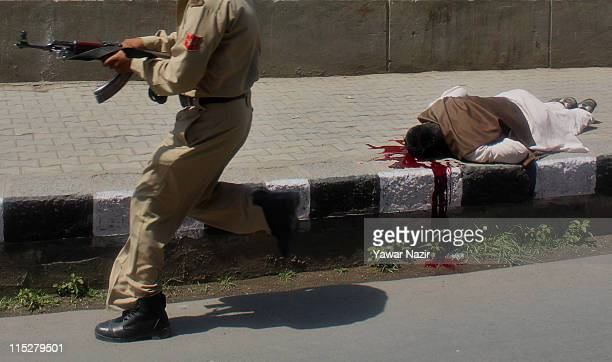 An Indian policeman takes position next a man who was shot by unidentified gunmen on June 6 2011 in Srinagar the summer capital of Indian...