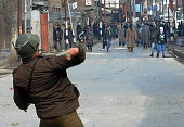 An Indian policeman throws a stone back toward Kashmiri demonstrators protesting against a military court verdict in downtown Srinagar on January 31...