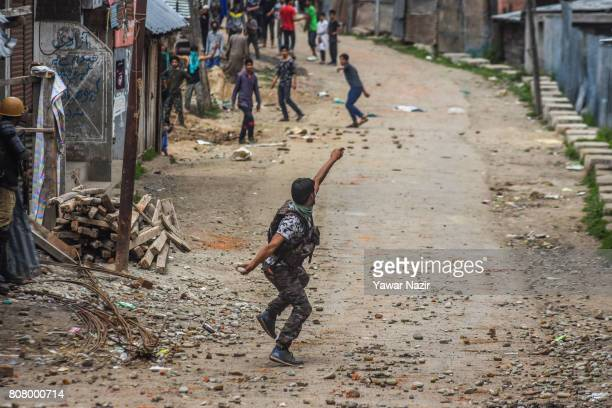 An Indian policeman throws stones at Kashmiri Muslims near the site after a gun battle between Indian government forces and rebels on July 4 2017 in...