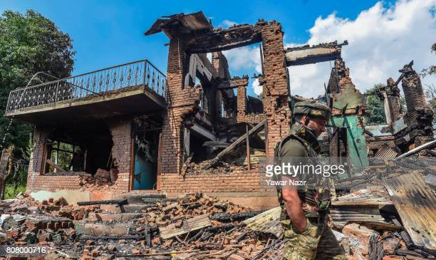An Indian policeman walks in front the war ravaged houses where from rebels were fighting with them after a gun battle on July 4 2017 in Bahmnoo 60...