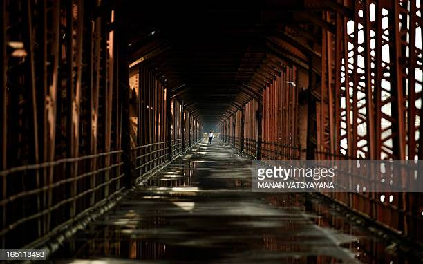 An Indian policeman walks on a deserted old bridge over the flooding Yamuna river in New Delhi on September 22 after it was closed for commuters and...