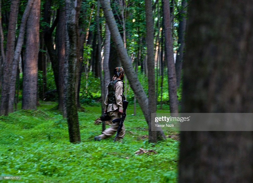An Indian policeman walks towards the site of a gun battle on June 1, 2013 in Wachi, 49 km (30 miles) south of Srinagar, the summer capital of Indian administered Kashmir, India. Two militants belonging to Hizbul Mujahideen, the largest militant outfit operating in Indian Administered Kashmir, were killed in the gun battle that started between militants and Indian military forces in South Kashmir yesterday and ended this evening, police said here. This was the second gun battle between militants and Indian military forces in South Kashmir in the span of one week. Last week, militants killed five Indian army soldiers, while a militant was also killed.
