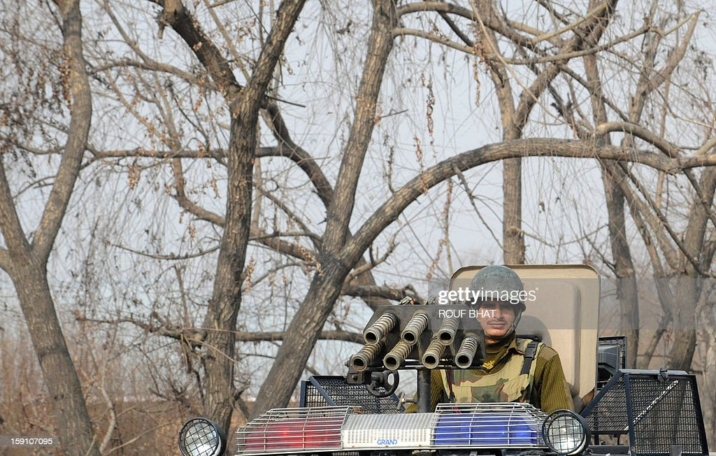 An Indian policeman watches Kashmiri demonstrators shouting slogans as they block a highway during a protest against electricity shortages in Srinagar on January 8, 2013. Kashmir Valley continued to reel under intense cold with temperatures plummeting further as Srinagar recorded the season's lowest of minus 5.5 degrees Celsius. AFP PHOTO/ Rouf BHAT