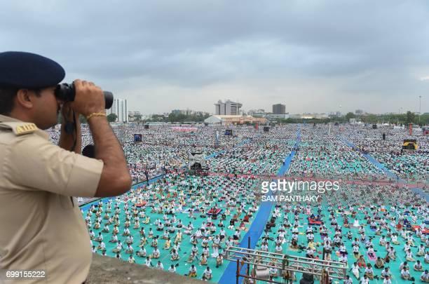 An Indian policeman watches over yoga enthusiasts taking part in a massive yoga workshop conducted by yoga guru Baba Ramdevji on International Yoga...