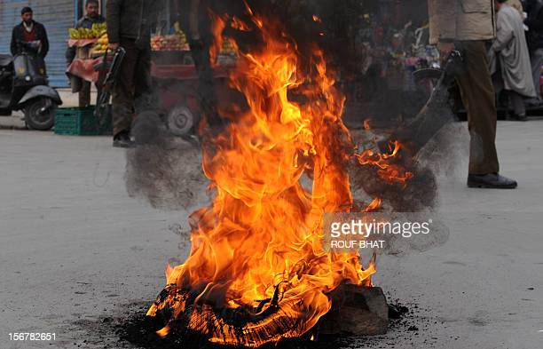 An Indian policeman wqalks past a burning tyre after the news that Pakistanborn Mohammed Kasab the sole surviving gunman from the 2008 Mumbai attacks...