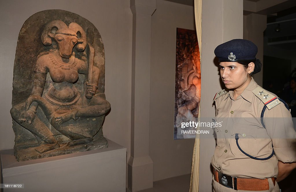 An Indian police-woman watches alongside the 10th century stone sculpture of the 400 kg, 4.5 foot high 'Yogini', inaugurated by Indian Minister for External Affairs, Salman Khurshid and Minister of Culture, Chandresh Kumari Katoch, at the National Museum in New Delhi on September 19, 2013. The 10th century sculpture of a female deity with a buffalo head was acquired by French art collector Robert Schrimpf from an unnamed source and donated by his widow, Martine Schrimpf to the Indian embassy in Paris in 2008.