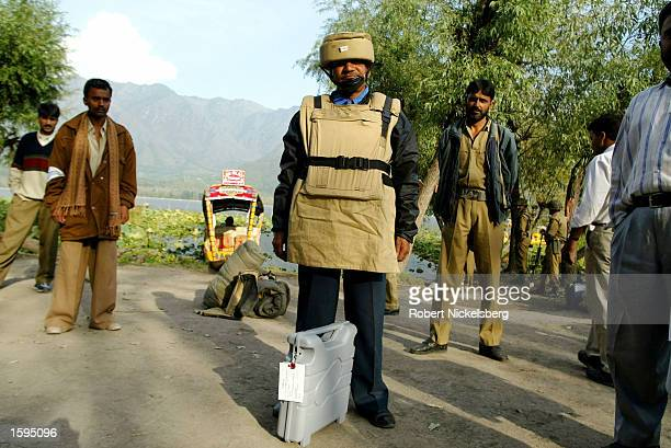 An Indian polling agent with a helmet and bullet proof vest waits for a boat to return to the main polling office with a sealed electronic voting...