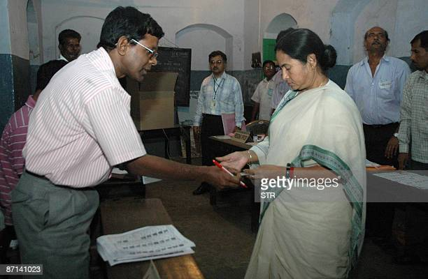 An Indian polling officer checks the voter identity card of the Leader of The Trinamool Congress Party Mamata Banerjee prior to casting her vote at a...