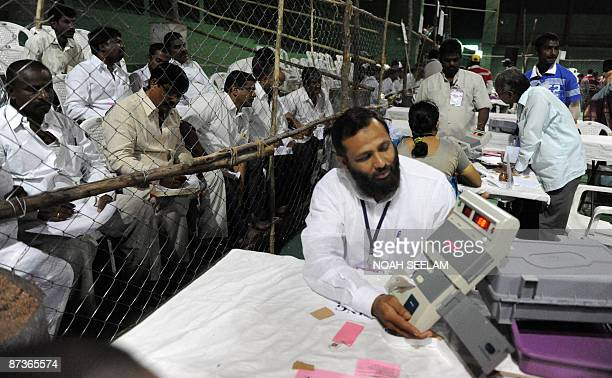 An Indian polling officer shows the number of votes on an Electronic Voting Machine to polling agents at a polling centre in Hyderabad on May 16 2009...