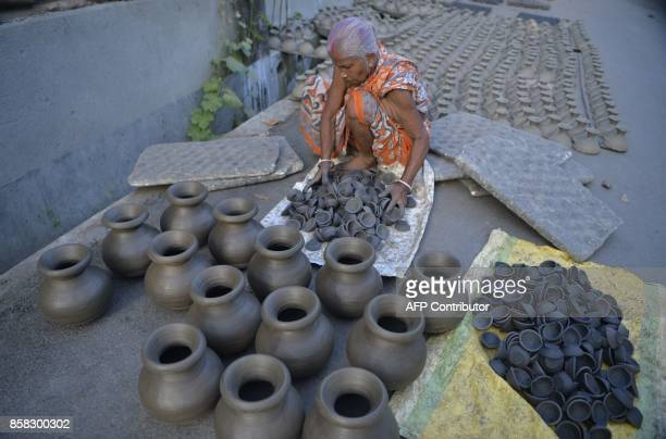An Indian potter arranges earthenware oil lamps or 'diyas' at a workshop ahead of the forthcoming Diwali festival in Siliguri on October 6 2017...