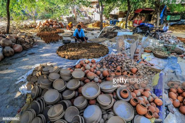 An Indian potter family members makes earthen lamps and other items ahead of Diwali festival in JaipurRajasthan India 08 Oct2017 People buy earthen...