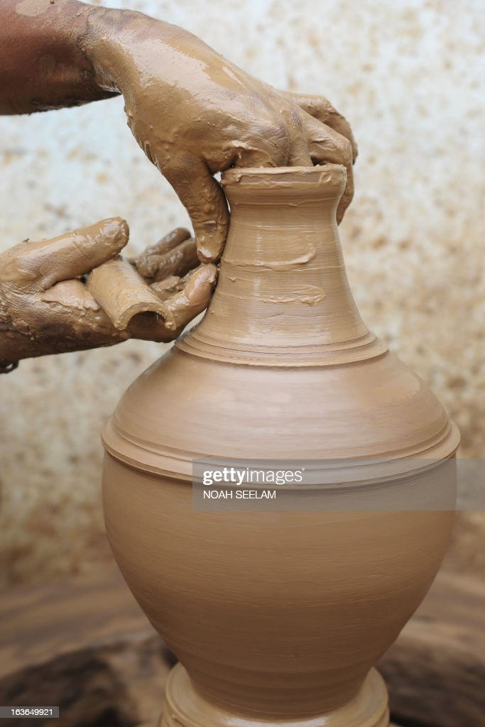 An Indian potter makes a traditional earthenware pot in Hyderabad on March 14, 2013. Earthenware pots, locally known as 'matkas', are traditionally used to store cool drinking water when temperatures dramatically increase during the hot summer months. AFP PHOTO / Noah SEELAM