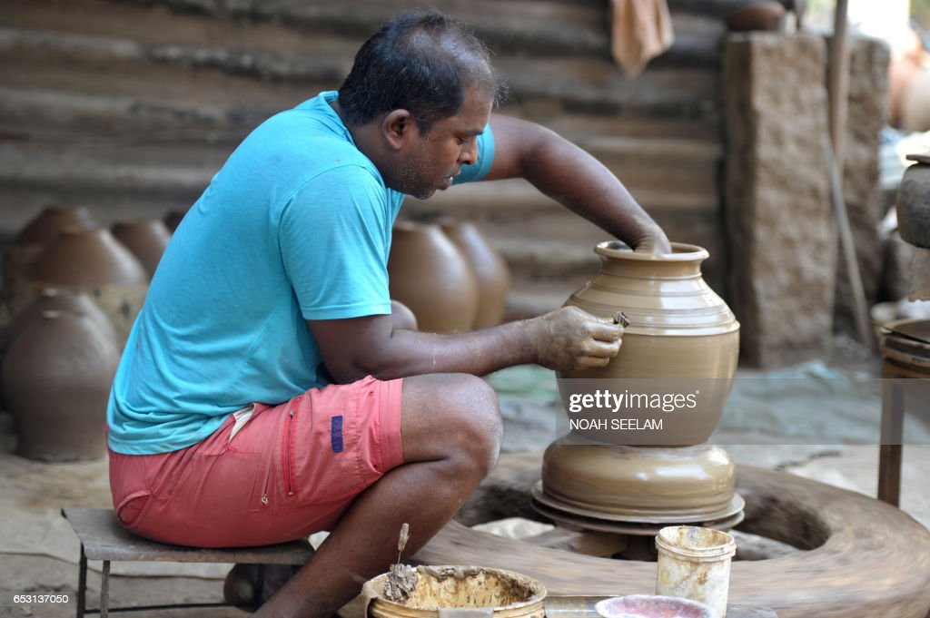 An Indian potter makes a traditional earthenware pot in Hyderabad on March 14, 2017. Earthenware pots, locally known as matkas, are used to store and cool drinking water when temperatures dramatically increase during summer. /