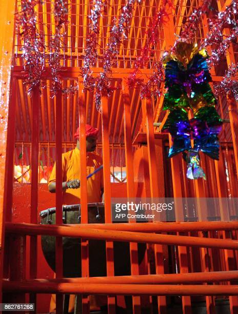 An Indian priest beats a drum during an Arti offering for Hanuman Jayanti at the Bade Hanuman temple near Sangam in Allahabad on October 18 2017...
